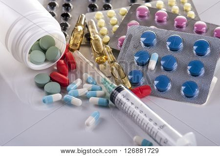 Pharmaceutical drugs syringe and capsules on white background.