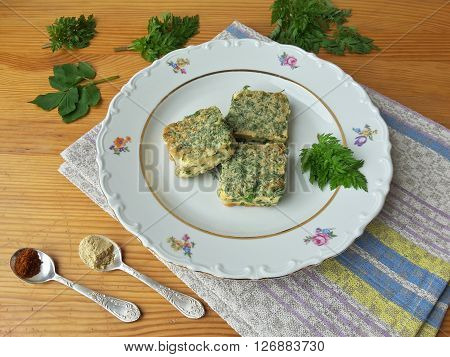 Tofu in green goutweed tempura on plate cooking organic food with wild plants, cow parsley and spices