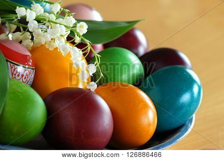 various colorful easter eggs on plate with may-lily flower