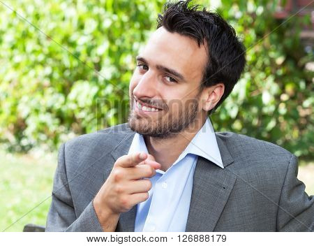 Pointing businesman in the park with meadow and green plants in the background