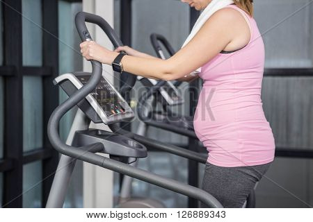 Pregnant woman on crosstrainer at the gym