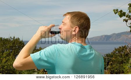 Man drinking red wine from glass it is on vacation. Man on the background of sky sea mountains and green plants. A man in a blue shirt tasting wine. South. Europe.