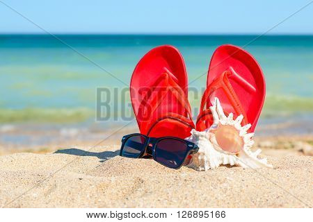 Slippers, Sunglasses And Shell In The Sand