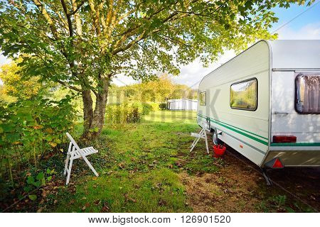 Caravan Trailer On A Green Lawn Under The Trees, On A Sunny Autumn Day. France