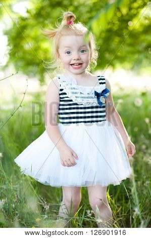 Smiling blonde child girl 2-3 year old playing outdoors. Wearing trendy striped dress over nature background.Childhood.