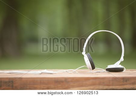 White headphones on old wooden table at the background of nature
