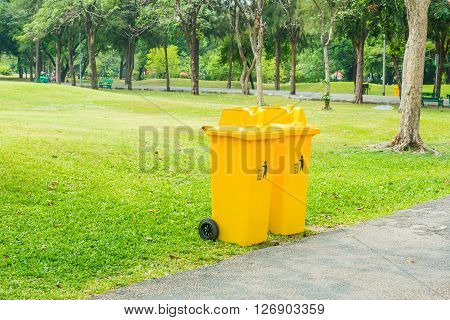 Close up of yellow plastic bin on ground in the park.