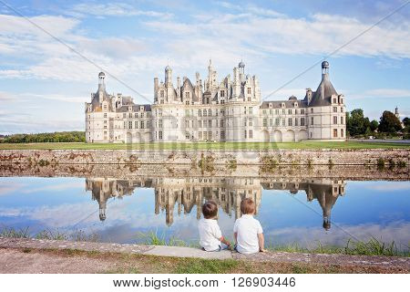 Happy family on Chambord chateaux enjoying summer holiday together