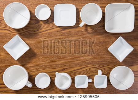 Empty plates and bowls on wooden background.