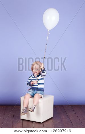 Cute baby girl 2-3 year old playing with balloon in room. Sitting on white chair. Wearing trendy clothes over purple. Childhood.