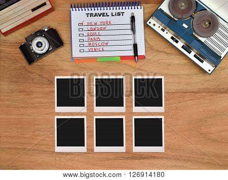 Old retro reel tape recorder vintage radio retro camera on wooden table. Six blank foto card.