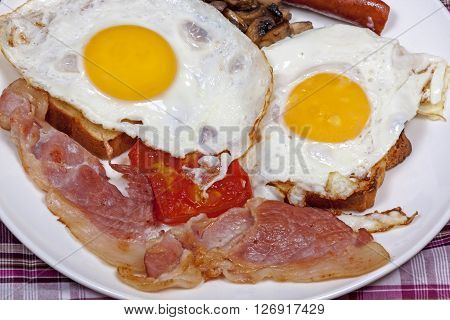 Fried Eggs On Toast With Tomato, Bacon And Mushrooms