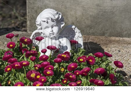 A white angel figure and red flowers