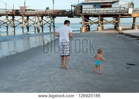 Dad and little son running along the shore of the Gulf of Mexico, Florida, USA