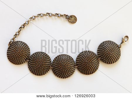 Jewelry traditional necklace of bronze embossed round links on white background