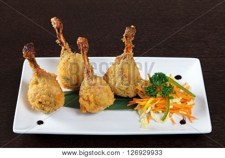 Kara-age. Fried chicken legs breaded and vegetarian side dish with sauce. Decorating a dish of Japanese and Asian cuisine. White dish on wooden background.