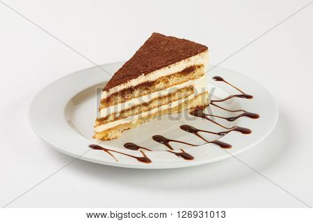 Delicious chocolate cream cake on the plate on white background. Close up side view.