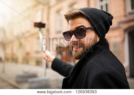 A photo of young trendy man taking himself a photo by his mobile phone on the selfie stick.