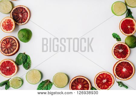 Red oranges yellow lemons green limes and mint frame isolated on white. Flat lay. Wraith frame