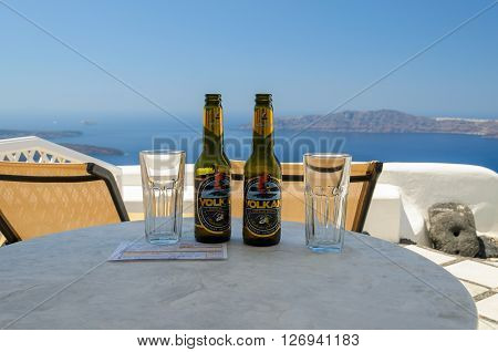 IMEROVIGLI, SANTORINI, GREECE - AUGUST 2013: Glasses and bottles of Volcano beer and a bill on table with blue sea on a background.
