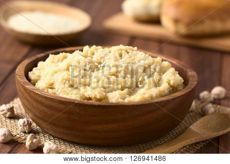 Chickpea spread or hummus with sesame seeds in wooden bowl photographed with natural light (Selective Focus Focus one third into the chickpea spread)