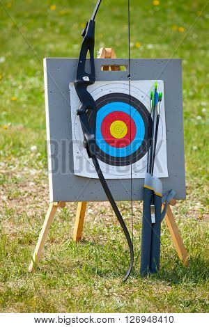 Bow and arrows with archery target outdoors