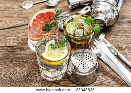 Fruit drinks with ice. Cocktail making bar tools shaker glasses mint leaves