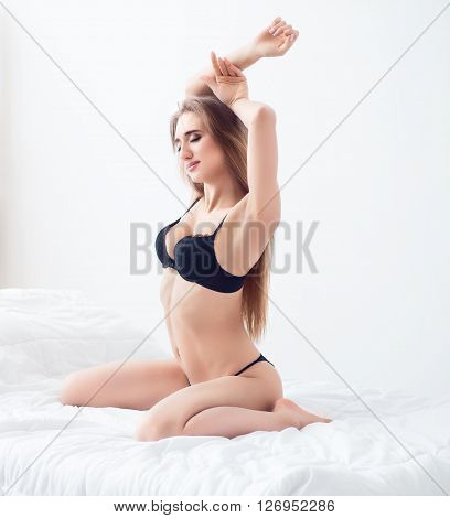 Feel the passion. Pleasant delighted attractive woman sitting in bed and closing her eyes in delight while seducing