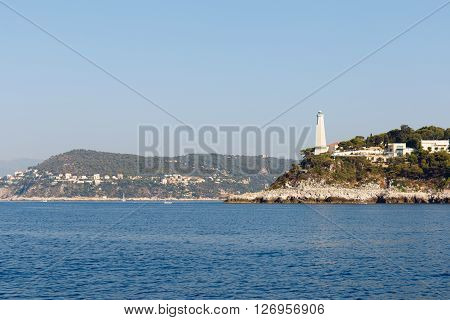 Color DSLR wide angle stock image of lighthouse and houses along the Mediterranean coast of the French Riviera near Nice, France. Horizontal with copy space for text