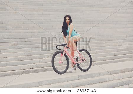 Sexy girl on bicycle. Young slim sexy sportive woman in blue shorts and white snickers long-haired, sensual posing on pink fix bicycle at grey stairs background. Soft toned.