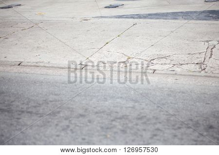 Broken sidewalk with metal caps and cracks