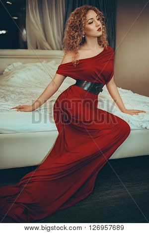 Sexy beautiful girl in evening dress on the bed