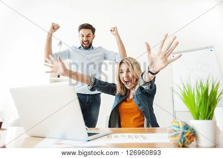 Cute two colleagues are celebrating their success. They are looking at laptop with satisfaction and raising arms up happily. Man and woman are smiling