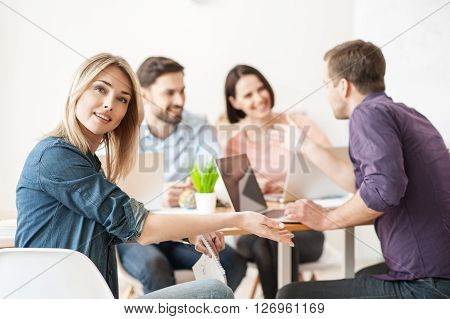 Look at my skillful team. Cheerful young woman is pointing arm at her colleagues are smiling. The men and women are sitting at desk and discussing a project