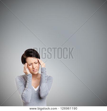Girl has a headache, isolated on grey