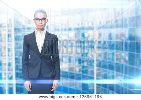 Half-length portrait of businesswoman wearing glasses with black frame, blue background. Concept of leadership and success