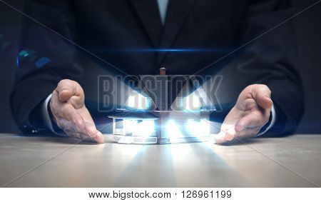 Close up of hands with house model shining. Concept of deal and realty poster