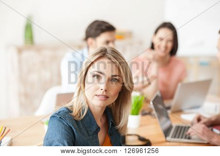 I like my work. Cheerful young woman is sitting near her colleagues. She is looking forward with confidence and smiling. The men and woman are communicating on background