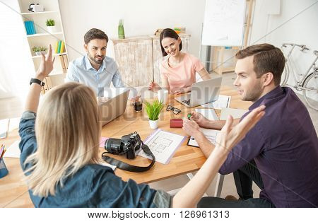 Pretty blond woman is explaining his idea about a project. She is raising arms with aspiration. Her colleagues are listening to her with interest and smiling