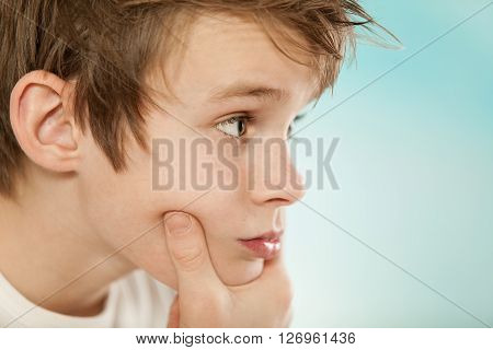 Thoughtful Young Boy Grasping His Chin