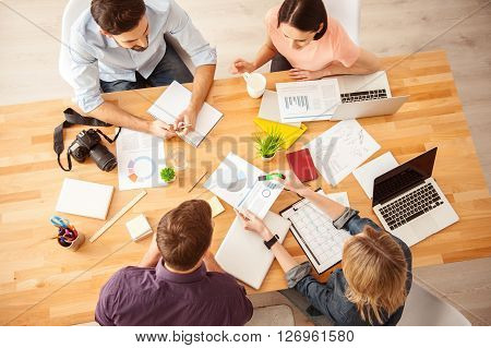 Top view of cheerful team working in cooperation. The woman is showing a paper and explaining her ideas. Her colleagues are sitting at desk and smiling