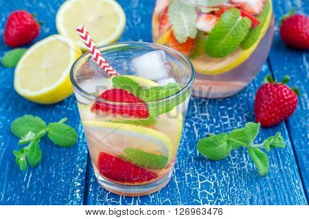 Strawberry mint homemade lemonade on blue wooden table ** Note: Shallow depth of field