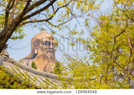 Laoshan China 21/04/2016 A huge 36m statue of the spiritual creator of Daoism Lao Tse seen through a forest above a Chinese roof