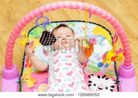 Happy little newborn baby with toys on the floor
