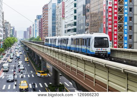 Taipei Taiwan - May 22 2014 : Street view of Taipei with metro train on the rail on May 22 2014 in Taipei Taiwan. the Taipei MRT is one of the best way to travel around the city.