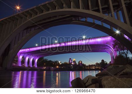 MINNEAPOLIS MINNESOTA USA - APRIL 22 2016: The I-35W bridge over the Mississippi River in Minneapolis is lit with purple lights in honor of the passing of music legend Prince.