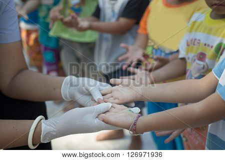 Yasothorn THAILAND DEC-01 : Health worker finding new case of Hand foot mouth disease in child on December 01,2015 at village in Yasothorn Thailand