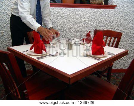 Waiter Setting Table In Restaurant