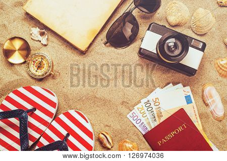 Summer vacation accessories on tropical sandy ocean beach holidays abroad - summertime lifestyle objects and European euros in flat lay top view arrangement in warm sand.