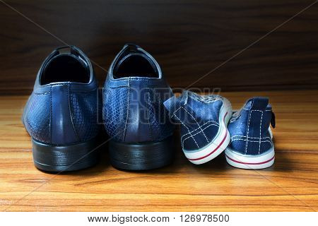 Men shoes and children sneakers from behind side by side on the wooden floor concept of family at home and father's day